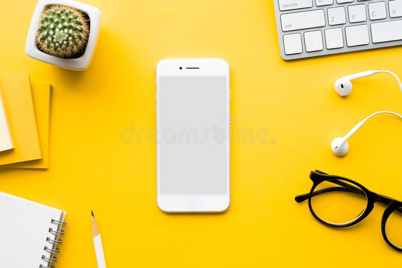 Top view of office desk table with mock up smartphone stock photography