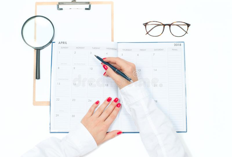 Top view office desk. Workspace with female hands, clipboard, calendar and glasses royalty free stock photos
