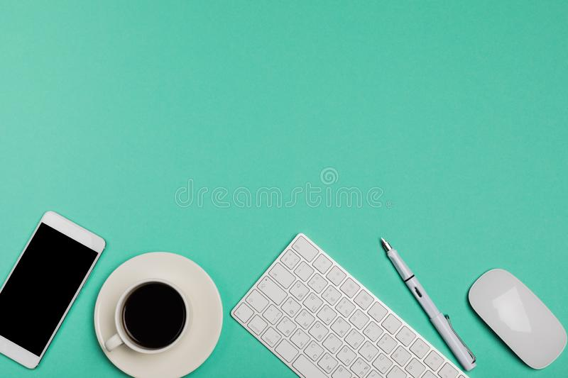 Top view of office desk workspace with smartphone, keyboard, coffee and mouse on blue background with copy space, graphic designer stock photo