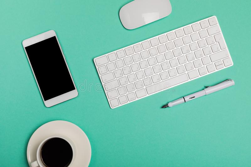 Top view of office desk workspace with smartphone, keyboard, coffee and mouse on blue background with copy space, graphic designer royalty free stock photography