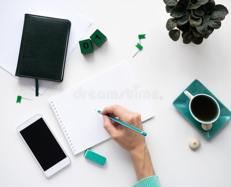 Workspace with blank notebook, smartphone, stationery, pencil, flower in a pot and a cup of tea with cookies on white background. royalty free stock photos