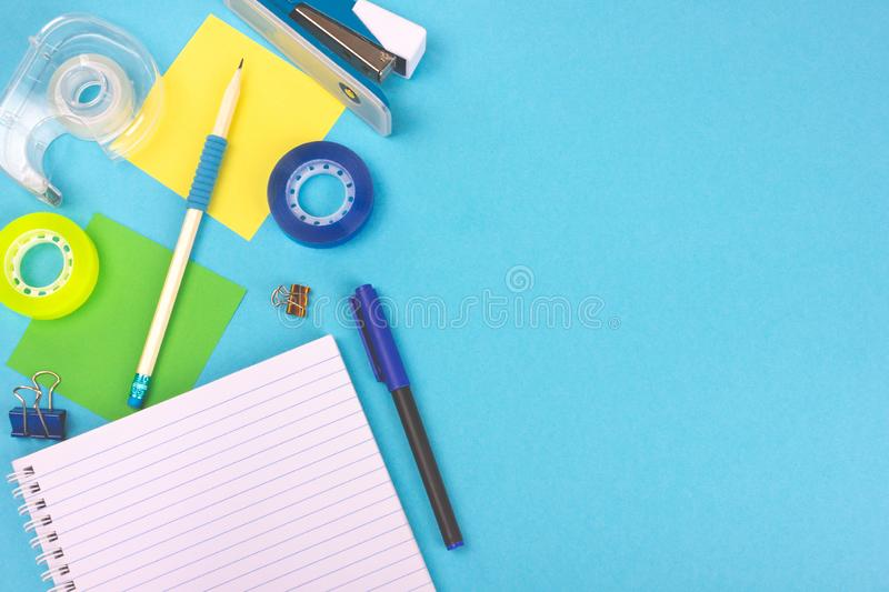 Top view of office desktop with school supplies. Top view of bright light blue office desk with school supplies. Back to school concept. Copy space for you text royalty free stock photos