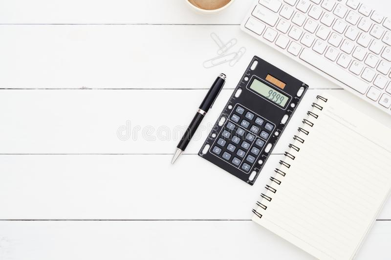 Top view office table desk.Table workspace with office accessories including wireless computer keybook, notebook, pen, calculator royalty free stock photo