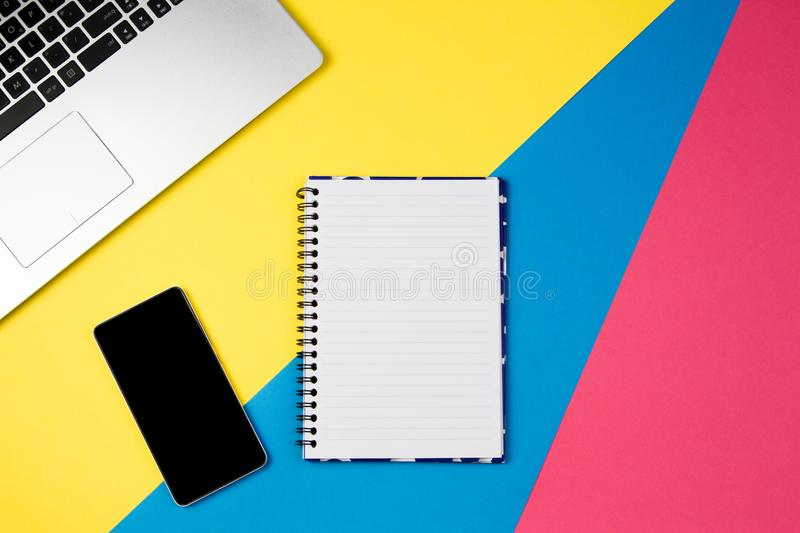 Top view office table desk. Workspace with laptop, smartphone and open spiral notebook page on colorful background. stock photos