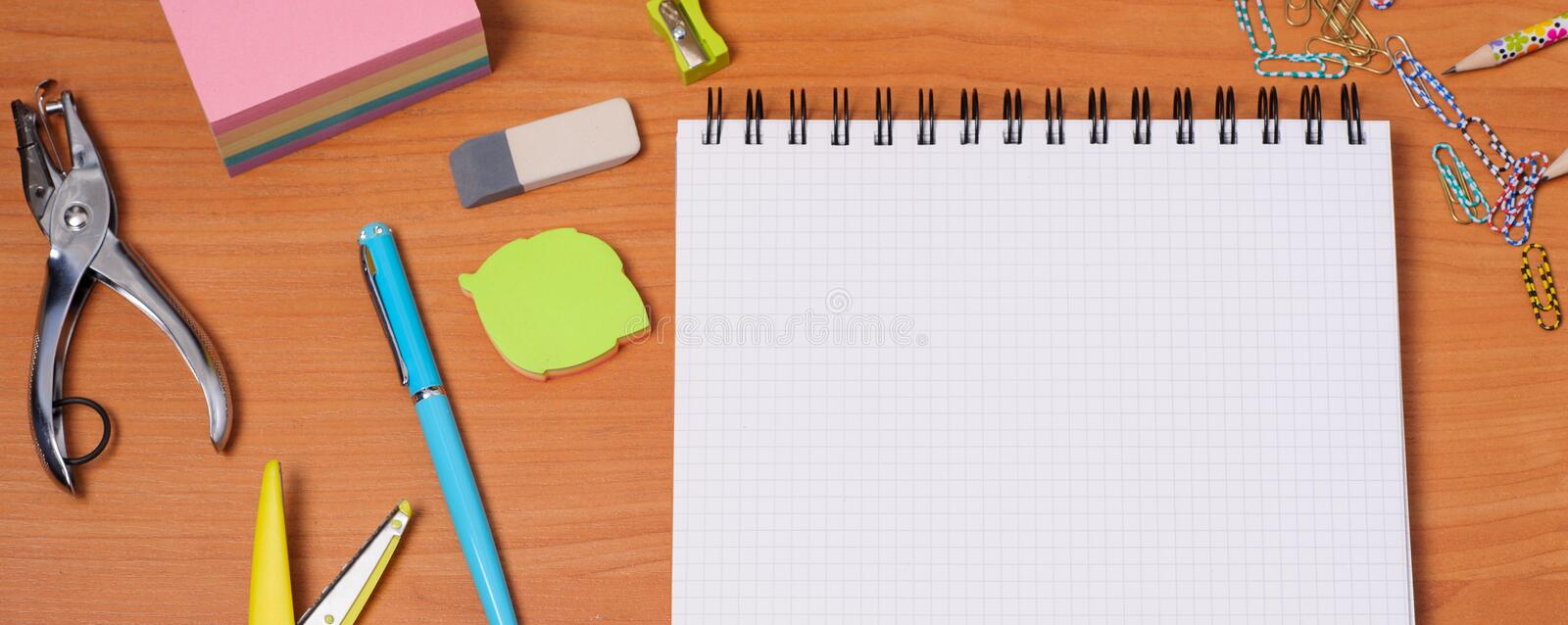Top view of office tools with blank notebook on wooden table royalty free stock photo