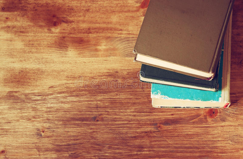 Top view of old books on a wooden table. retro filtered image stock image