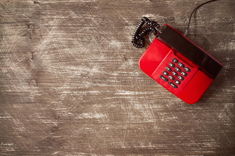 Top view of old fashioned telephone. Top view of old fashioned telephone on wooden background with copy-space stock images