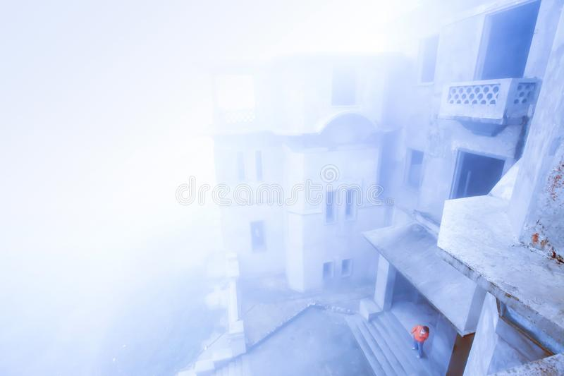Top view of old French colonial building in foggy, atop Borkor Mountain, Kampot, Cambodia. Top view of old French colonial building in foggy, a tourist standing royalty free stock photography
