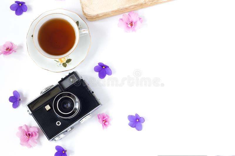 Top view of old retro camera and old book on white background with pink flowers and cup of coffee or tea.  royalty free stock photography