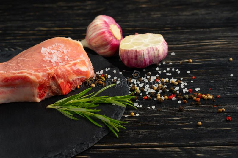 Top view of one pieces raw pork chop steaks with on a black stone cutting board. Top view of one pieces raw pork chop steaks with garlic sea salt red black royalty free stock images