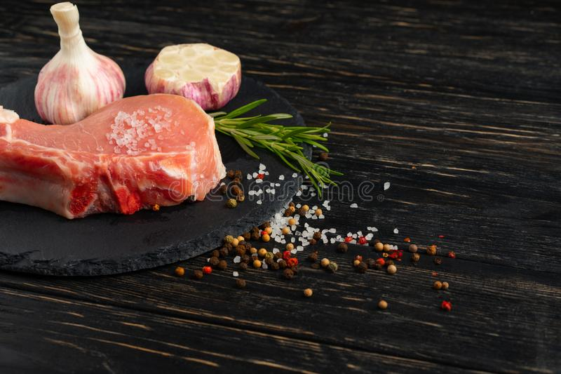 Top view of one pieces raw pork chop steaks with on a black stone cutting board. Top view of one pieces raw pork chop steaks with garlic sea salt red black royalty free stock image