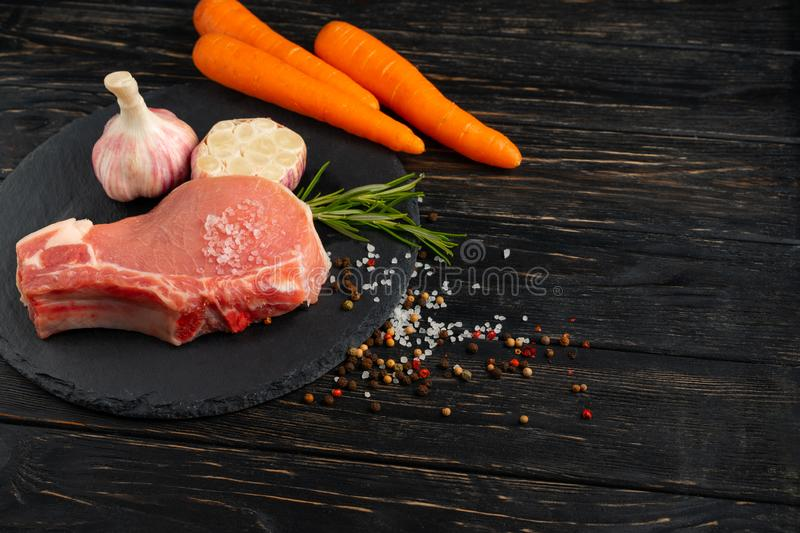 Top view of one pieces raw pork chop steaks with on a black stone cutting board. Top view of one pieces raw pork chop steaks with carrot garlic sea salt red stock photography