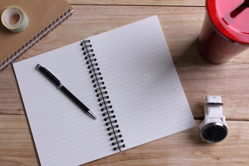 Top view Open book with blank pages and pen with clock with Stai. Nless steel and tumbler cup on wooden background stock photos