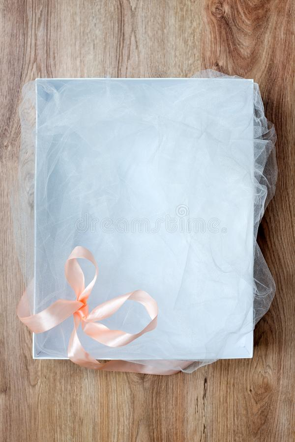 Top view of open empty gift box on wooden table. White gift box with ribbon bow. Present on holiday. Free space for text royalty free stock photos