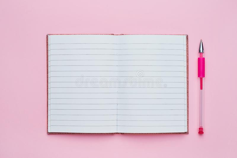 Top view of an open notebook with blank page and pink pen. Back to school concept stock photography