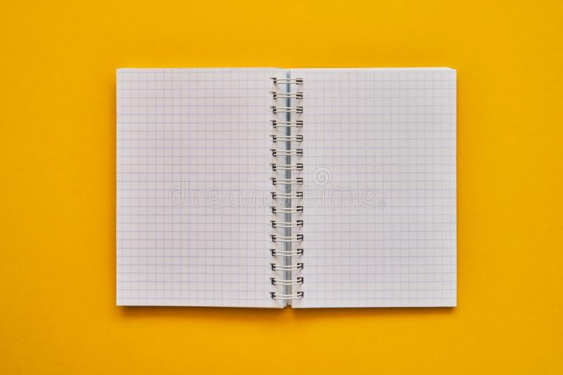 Top view of open notebook with blank pages. school notebook on a yellow background, spiral notepad stock photos