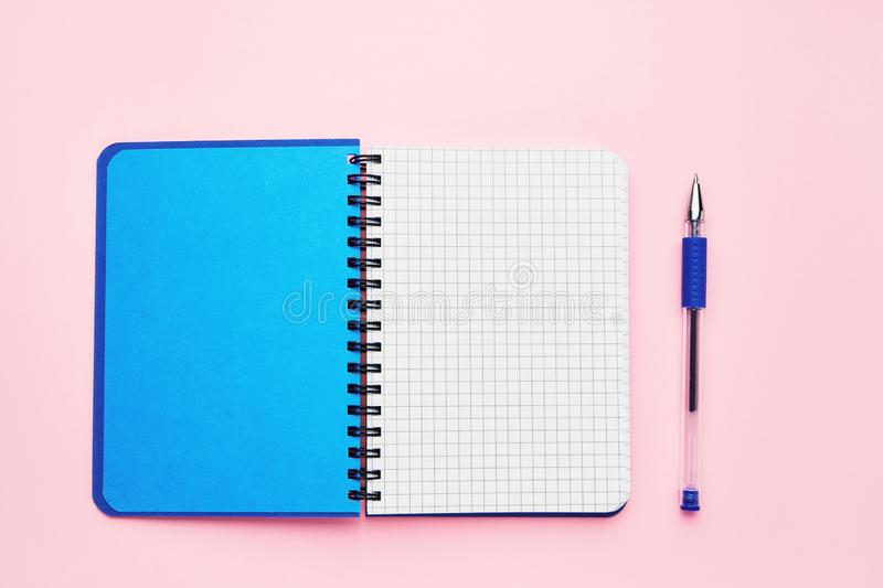 Top view of an open notebook with blank squared pages and blue pen. School notebook on a pink background. Back to school concept royalty free stock image