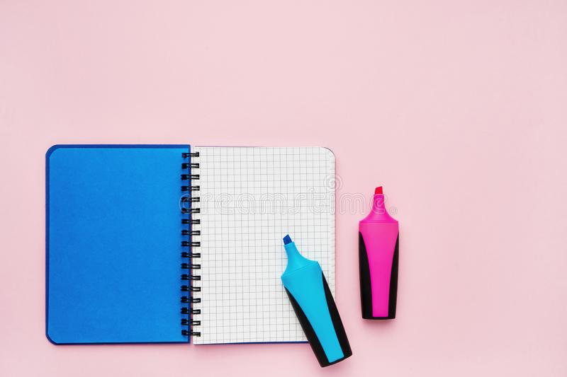 Top view of an open notebook with blank squared pages and felt tip pens. School notebook on a pink background, spiral notepad. royalty free stock images