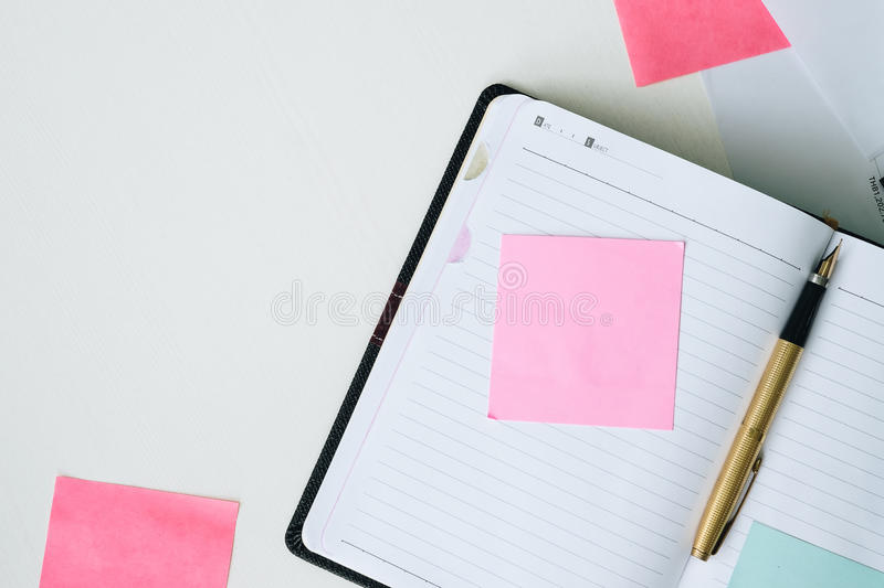 Top view open notebook, pen and post it on white desk background stock photo