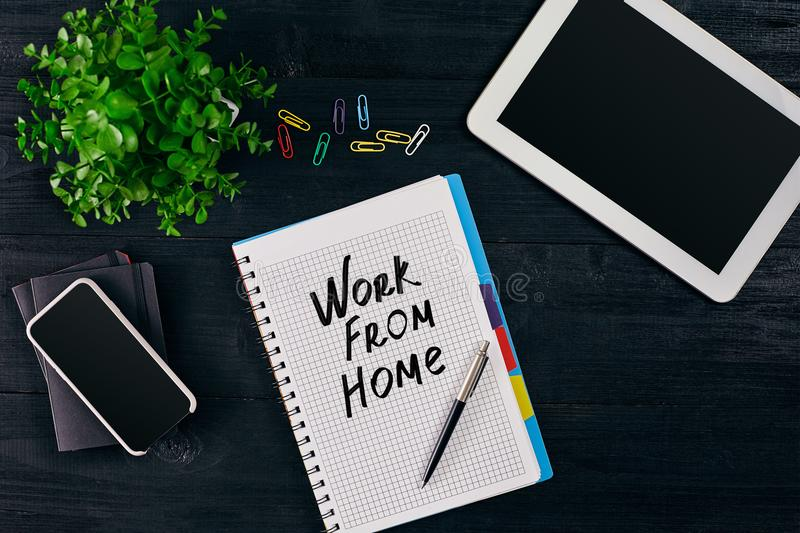 Top view of open notebook written with WORK FROM HOME inscription. Green flower, tablet, colored paper clips, smart, pen. And notebook on wooden background stock images