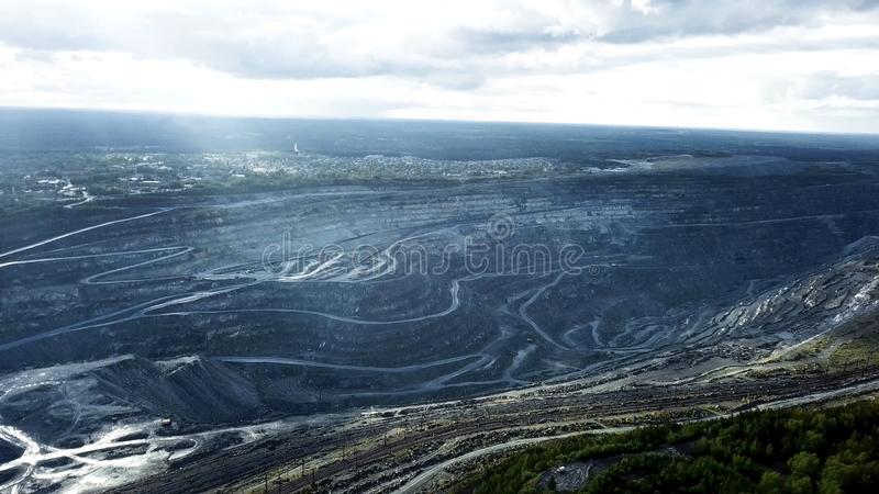 Top view of open quarries. Panoramic view of standing gray dust over open pits with working trucks. Mining industry. Conception stock photo