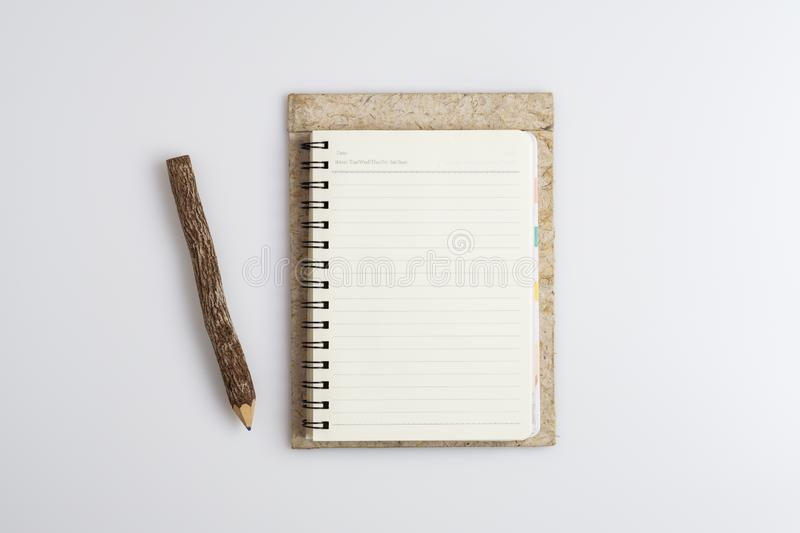 Top view of open spiral blank notebook with nature wooden pencil on white desk background royalty free stock image