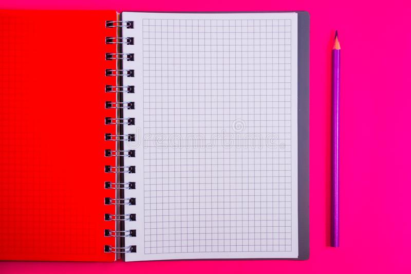Top view of open spiral blank notebook with pencil on red desk background. Top view of open spiral blank notebook with pencil on a red desk background stock image