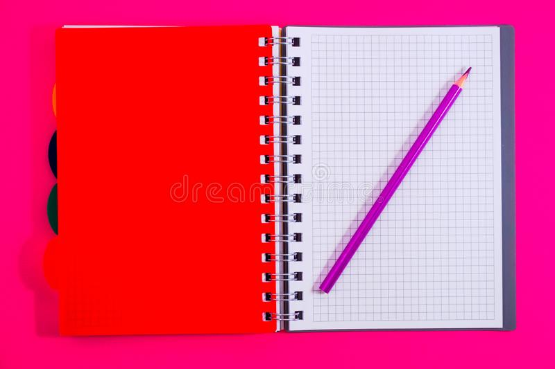 Top view of open spiral blank notebook with pencil on red desk background. Top view of open spiral blank notebook with pencil on a red desk background royalty free stock images