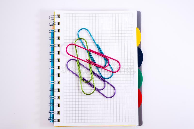 Top view of open spiral blank notebook with pencil on white desk background. Top view of open spiral blank notebook with pencil on a white desk background stock image