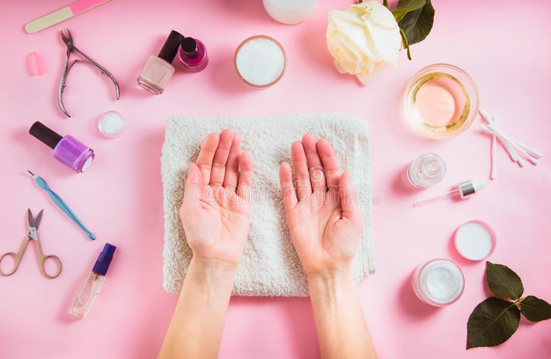 Top view opened female hands on the white towel surounded cosmetics and accessories for manicure and skin care. Flat lay royalty free stock photo