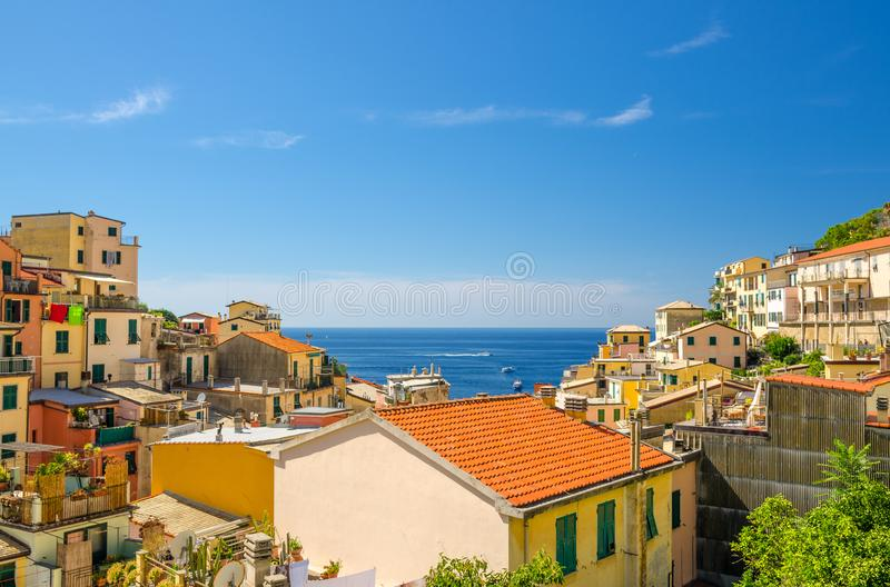 Top view of orange tiled roofs of multicolored houses with balconies and shutter windows of Riomaggiore typical fishing village Na royalty free stock images