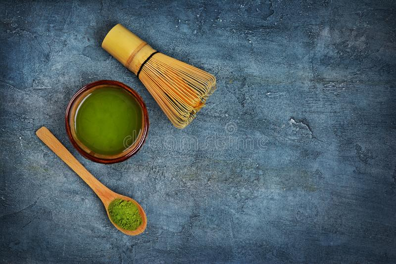 Top view on organic green matcha tea�in bowl with bamboo whisk and wooden spoon. On blue concrete background with copy space royalty free stock photography