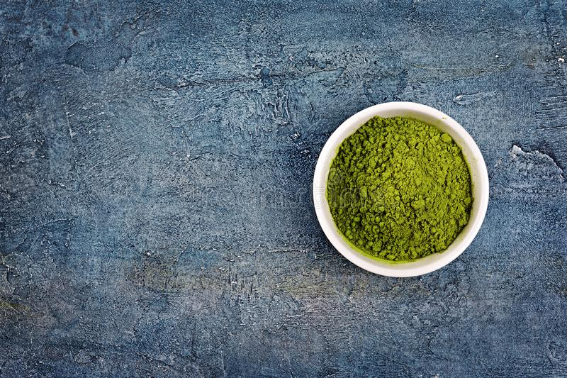 Top view on organic green matcha tea�powder on blue concrete background. Top view on organic green matcha tea�powder in white bowl on blue concrete royalty free stock image