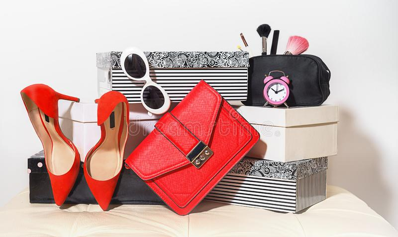 Top view outfit layout trendy female accessories red shoes handbag clutch sunglasses cosmetics alarm clock on carton boxes on royalty free stock photos