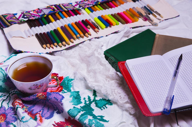 Top view of paint, a blank sheet of paper, cup of tea, markers. Top view of paint, a blank sheet of paper, cup of tea, markers , Workplace concept royalty free stock photography
