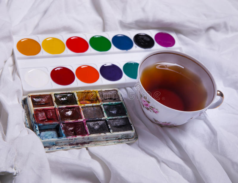Top view of paint, a blank sheet of paper, cup of tea, markers. Top view of paint, a blank sheet of paper, cup of tea, markers , Workplace concept stock photo