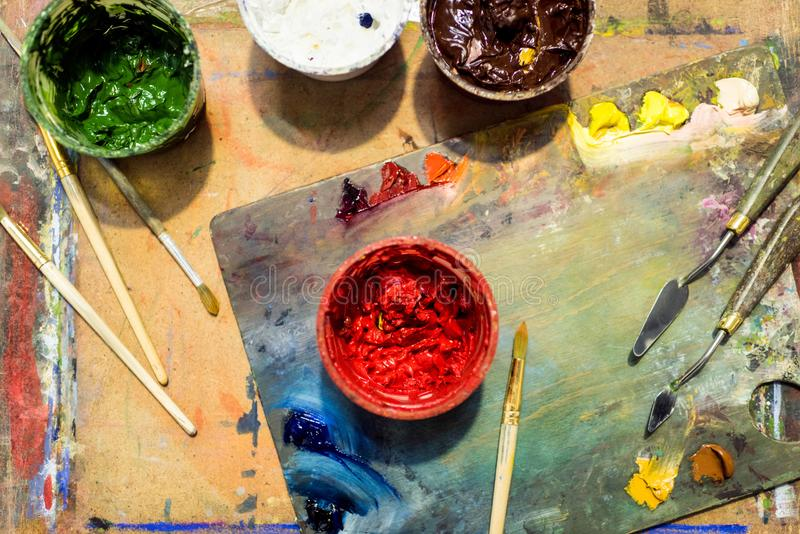 top view of painting brushes, palette and poster paints on wooden table royalty free stock images