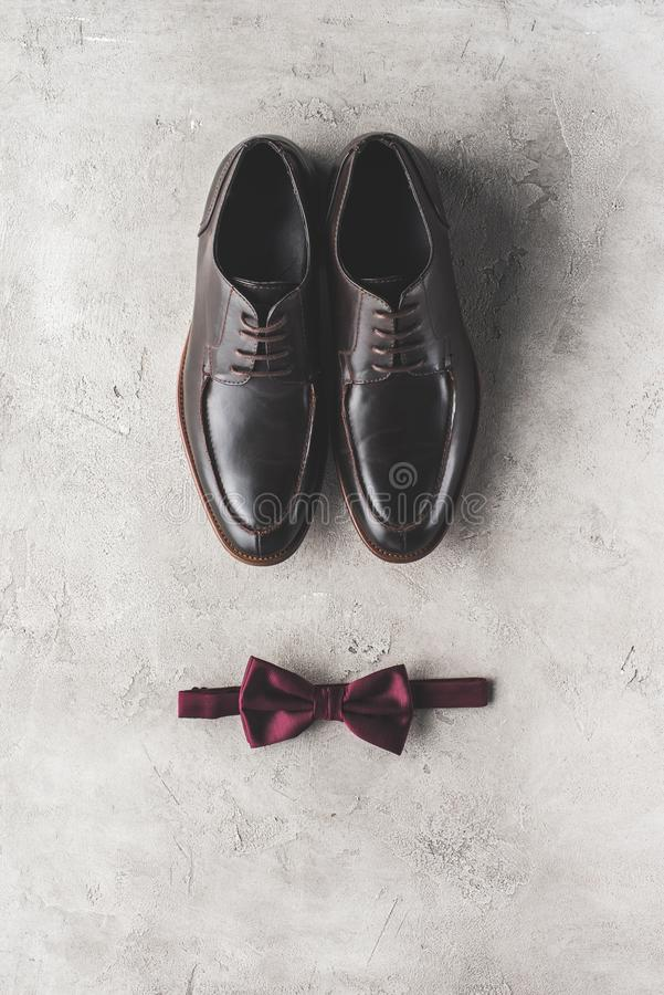 Top view of pair of black wedding shoes and bow tie. On gray surface royalty free stock photo