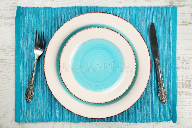 Top view of a pair of empty salad and dinner plates with a teal blue well and vintage fork and knife on a turquoise napkin and whi royalty free stock photos