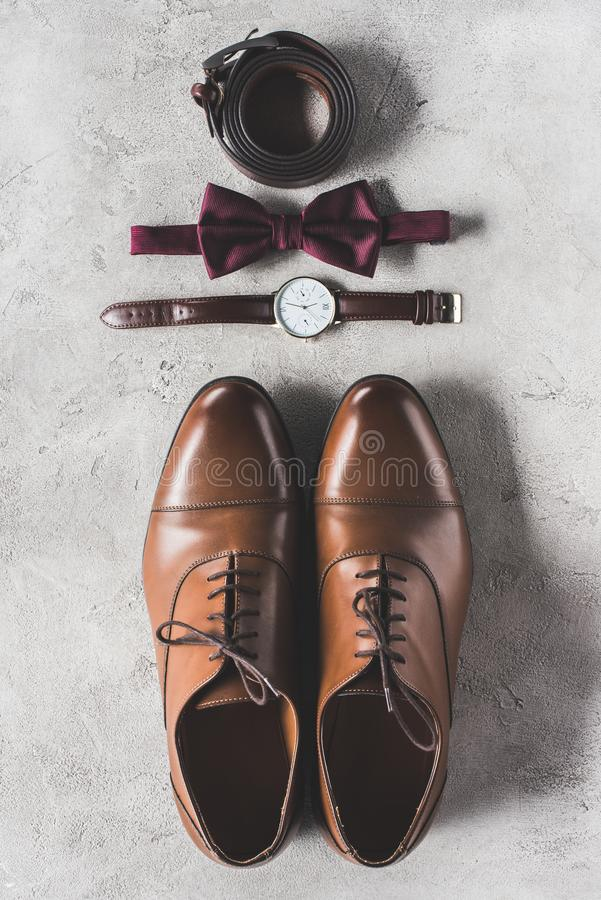 Top view of pair of wedding shoes, bow tie and wristwatch. On gray surface royalty free stock images