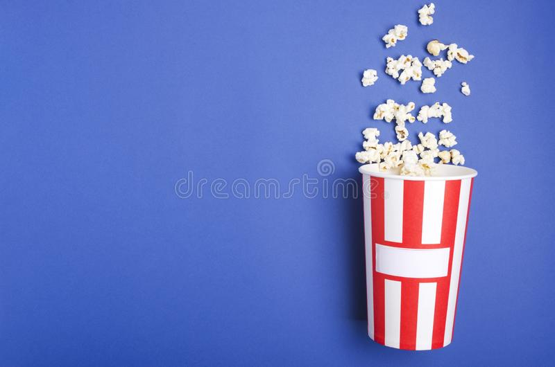 Top view of paper box for pop corn, fresh salty pop corn on the dark blue surface royalty free stock image