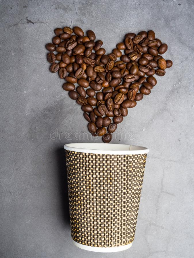 top view paper coffee to go cup and heart made from coffee beans, , copy space, grey background royalty free stock images