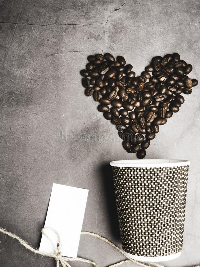 Top view paper coffee to go cup and heart made from coffee beans, decorative thread, mock up paper cup, copy space. Top view paper coffee to go cup and heart stock photos