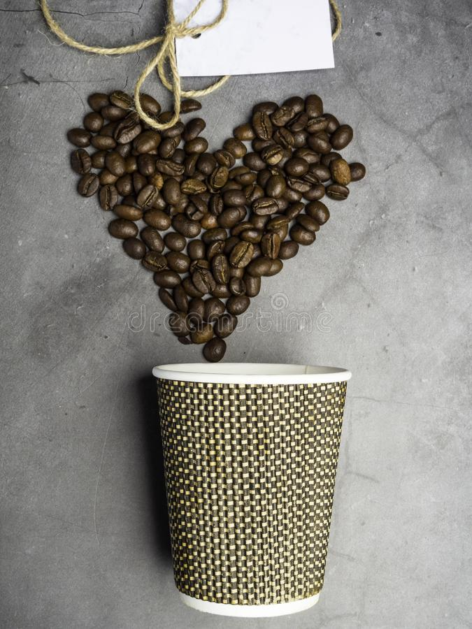 Top view paper coffee to go cup and heart made from coffee beans, mock up paper cup, copy space. Top view paper coffee to go cup and heart made from coffee beans royalty free stock photography