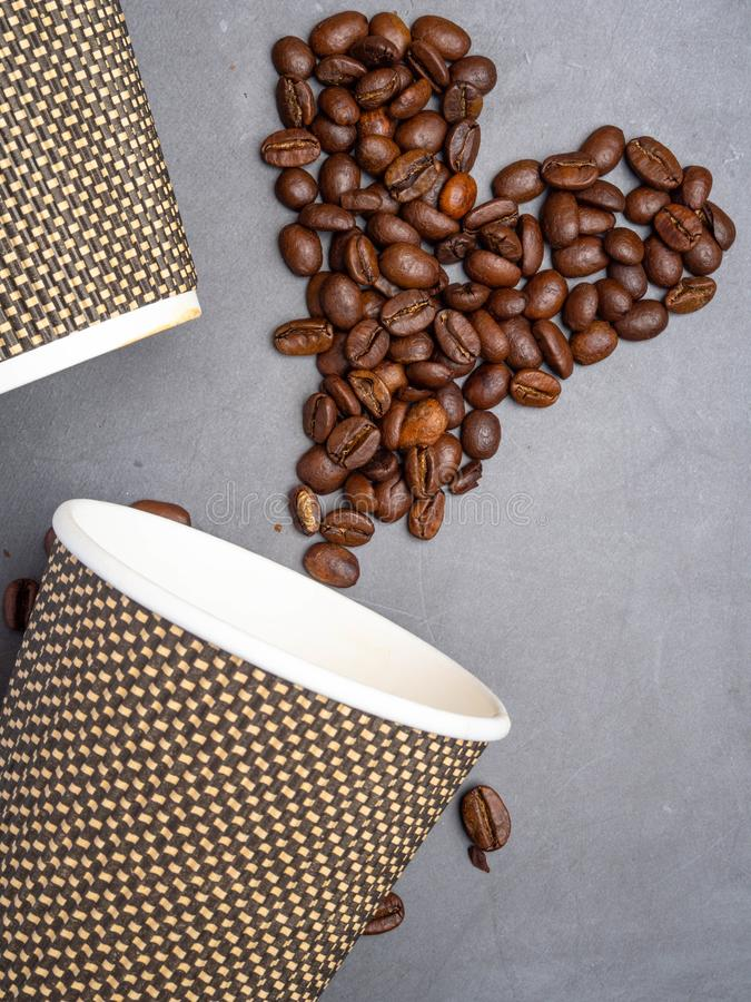 Top view paper coffee to go cups and heart made from coffee beans, mock up paper cups, copy space. Concrete grey background royalty free stock photos