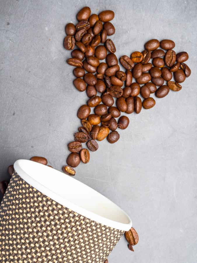 Top view paper coffee to go cups and heart made from coffee beans, mock up paper cups, copy space. Concrete grey background stock image