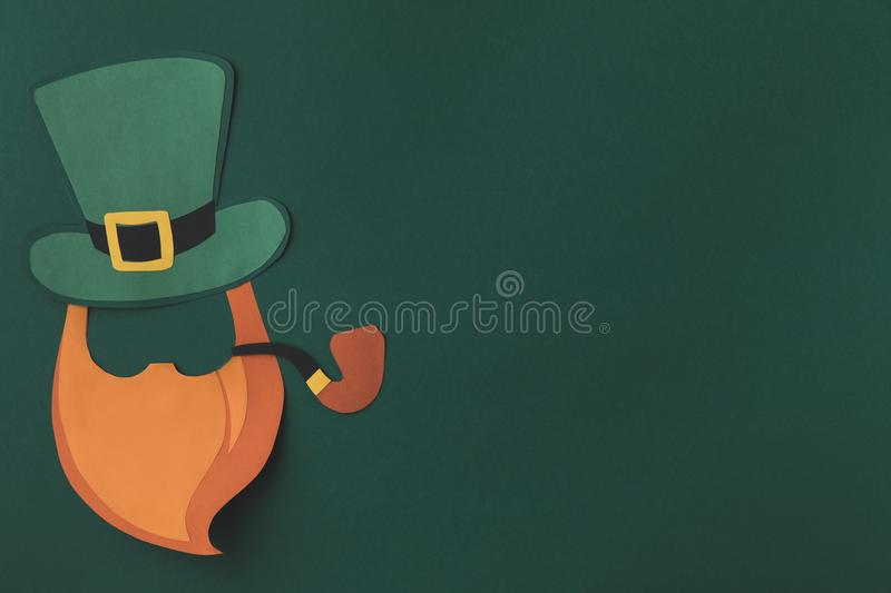 Top view of paper decoration of man with smoking pipe for st patricks day. Isolated on green royalty free stock photo