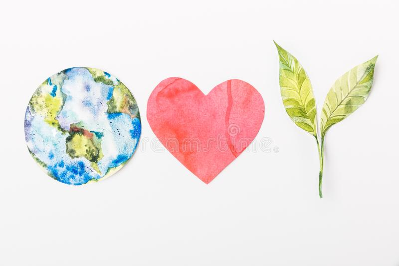 Top view of paper made colorful globe, red heart and green plant isolated on grey, recycling and environment protection concept stock photos