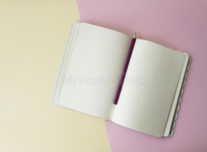Top view of  paper notepad with color pencil and blank sheets with dots on light pink yellow background. royalty free stock photo