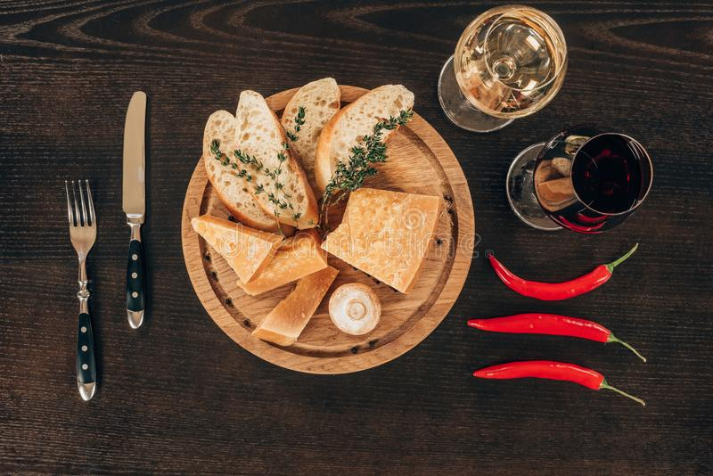 Top view of parmesan cheese with baguette slices on wooden board, chili peppers and wine. On table royalty free stock photography